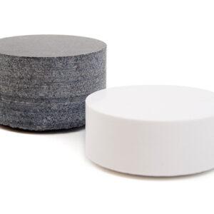 Svart och vit stenpuck i granit respektive marmor.